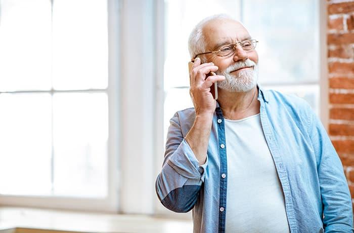 Smiling senior old man making a phone call