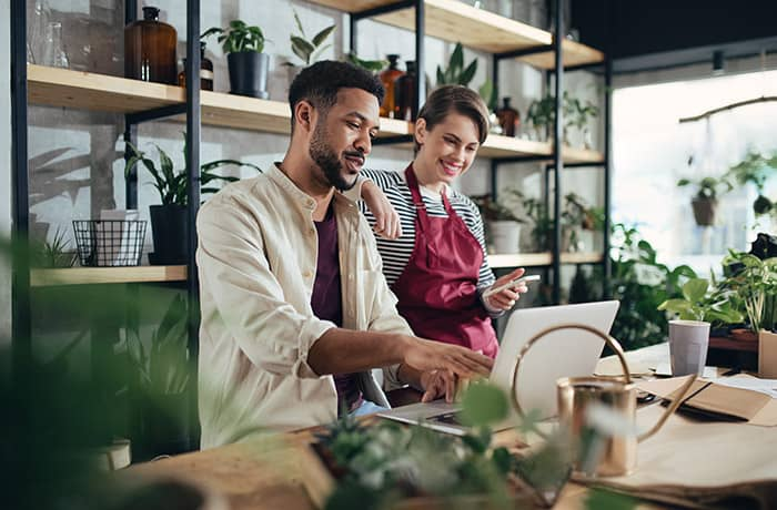 A man showing how the idea of this new business is going to work while the lady is happily watching it and holding the phone to give a final go ahead after it with a beautiful background filled with plants